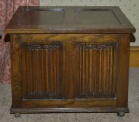 An oak coffer, 20th century of small proportions with two panelled top and two linen fold carved