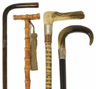Three late 19th/early 20th century walking canes and later umbrella including a walking cane with