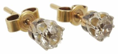 A pair of single stone diamond set stud earrings each stone approximately 0.25ct, yellow metal
