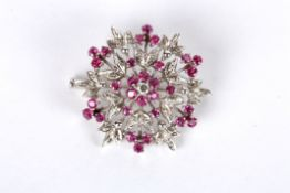 A Continental ruby and diamond set floral circular cluster brooch with central diamond and ruby