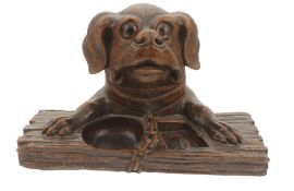 A dogs head inkwell desk stand, 20th century modelled as a dogs head and paws resting upon a plank