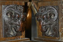 A pair of carved oak rams heads, 19th century each depicting a rams head upon a rectangular carved
