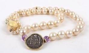 An unusual cultured pearl and coin necklace the pearls graduated to either side and set with a