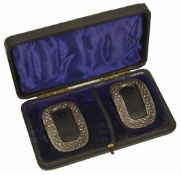 A cased set of early 19th cut steel and leather buckles of oval form with cut steel border and
