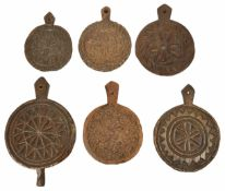Six carved treen butter moulds, 19th century and later each of circular form with pierced handle and