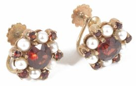 A pair of 9ct gold garnet and pearl set circular cluster earrings with central garnet with