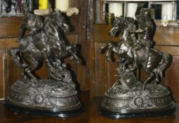 A pair of large early 20th century Spelter figures of warriors on horseback each on ebonised oval
