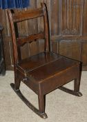 An oak child's rocking chair, 19th century the slatted back above panelled seat with a side drawer
