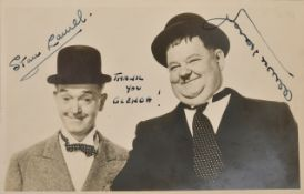 A signed black and white publicity photograph of Laurel and Hardy signed in black ink by Stan Laurel