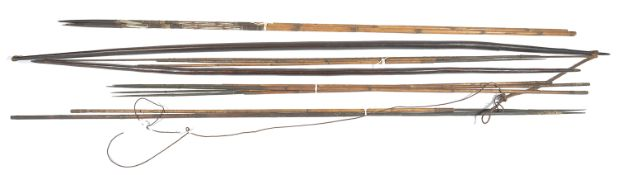 A collection of African tribal arrows and bows, the two bows of tapering form with pointed ends, one