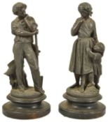 A pair of spelter figurines, 20th century modelled as a lady with a boy at her side and the other as