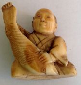 A small ivory Japanese okimono figure the realistically carved figure of seated gentleman holding