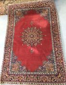 An early 20th century Persian carpet, the quartered madder field with central floral medallion
