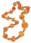 An impressive butterscotch amber bead necklace formed of graduated large polished disc shaped