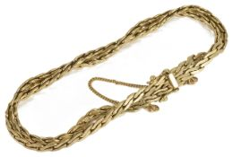 A Continental .585 gold flat weave twin chain bracelet the articulated chains twisted together and