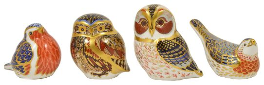 Four Royal Crown Derby paperweights in the form of birds including two owls, a robin and another,