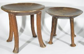 Two 20th century African tribal stools, each with dished seats upon four supports, together with a