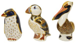 A group of three Royal Crown Derby paperweights the first modelled as a brown pelican, the second