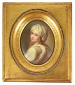 An oval porcelain painted miniature of a girl, early 20th century modelled looking over her left