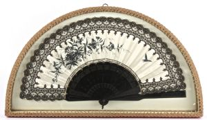 An Edwardian ladies fan in a demi-lune display case the cream satin painted in black with floral