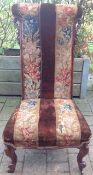 A Victorian mahogany prie-dieu chair with cabriole legs to the front and upholstery with tapestry