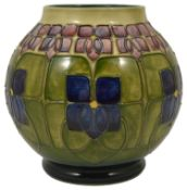 A Moorcroft tube lined Violet vase, by William John Moorcroft the bulbous body with violet