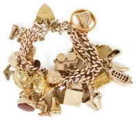 A heavy 9ct gold rose gold double curb link charm bracelet hung with a variety of gold charms