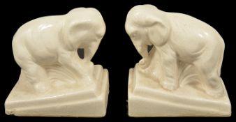 A pair of porcelain glazed elephants, 20th century modelled standing upon rectangular sloped