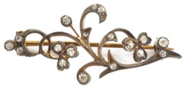 A delicate Edwardian rose diamond set floral scroll brooch formed as a softly curved single
