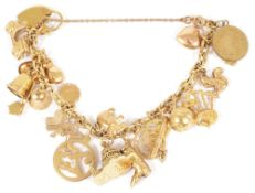 A selection of mainly 9ct gold and yellow metal charms suspended from a gilded metal bracelet, 9ct