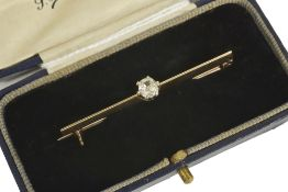 An early 20th century old cut diamond set bar broochthe single diamond mounted on a yellow metal