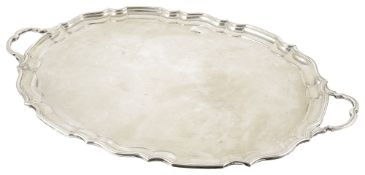 An impressive George V silver twin handle tray, Sheffield 1919of oval pie crust from with two shaped
