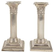 A pair of silver dwarf candlesticks, Birmingham 1908with beaded concave drip trays above