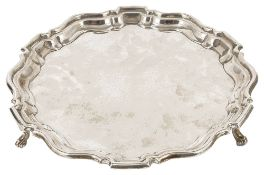An Edwardian silver salver, London 1904with pie crust stepped edge raised upon three scrolled
