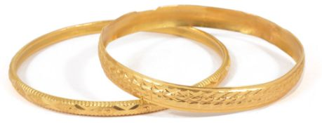 Two Eastern yellow metal bangles, test for high carat goldeach with bright cut decoration (2)approx.