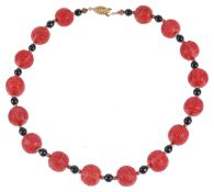A reproduction Chinese red lacquer bead necklace,