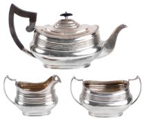 An Edwardian three piece tea service, hallmarked Sheffield 1918the teapot with ribbed body and