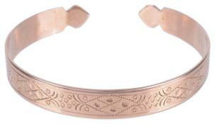 An early 20th century scroll engraved open banglethe rose coloured metal with floral and scroll