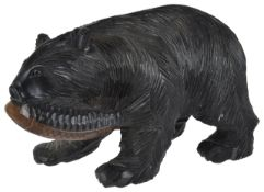 A German Black Forrest bear with fish the bear realistically carved in walking pose with fish