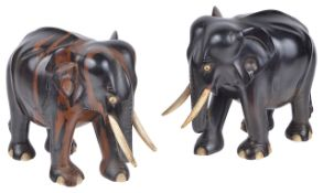 A pair of Indian hardwood elephants, 20th centuryeach standing with bone tusks and eyes, a/f, (2)