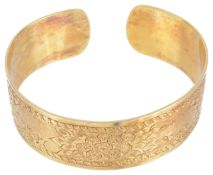 A wide Continental yellow metal engraved cuff bangledecorated with flower posies on a plannished