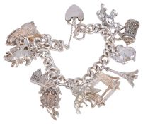 A heavy silver curb link charm braceletthe bracelet hung with a variety of charms including an