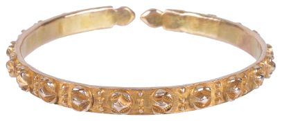 An early 20th century rose metal bangle of unusual raised floret designeach floret with bead work
