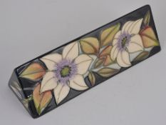 A contemporary Moorcroft pottery triangular shaped promotional stand by Sian Leeper