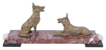 An Art Deco style mantelpiece a pair of spelter dogs one seated and the other lying upon a stepped