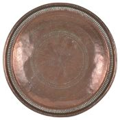 A large Islamic circular copper tray with bead and fluted border