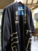 TWO ORIENTAL BLACK KIMONO, ONE OF WOVEN LINEN WITH GEOMETRIC DECORATION AND CHARACTERS TO THE