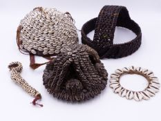 AN AFRICAN TRIBAL COWRIE SHELL HEADDRESS,ANOTHER OF SKULL CAP FORM AND TWO SIMILAR ADOURNMENTS, LEGA