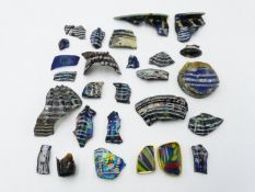 A COLLECTION OF TWENTY FIVE EGYPTIAN COLOURED AND DECORATED GLASS FRAGMENTS, THE LARGEST APPROX 10