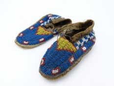 A PAIR OF NATIVE NORTH AMERICAN INDIAN CHILD'S BEADED MOCCASINS.